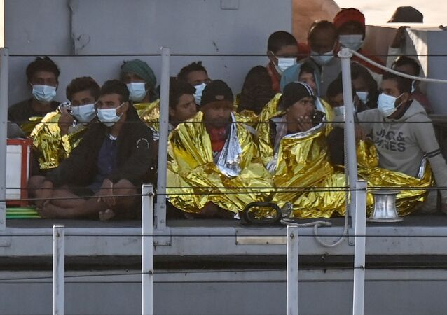 Migrants warmed by emergency blankets arrive on a boat of the Italian Guardia Di Finanza law enforcement agency on May 17, 2021 to disembark on the southern Italian Pelagie Island of Lampedusa. - More than 1,400 migrants arrived on the Italian island of Lampedusa at the weekend, sparking calls from far-right politicians for action to stem the flow, amid fresh moves by Italian authorities against the rescue boats who operate in the central Mediterranean.