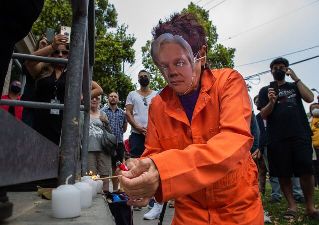 A woman wearing an orange jumpsuit and Julian Assange mask, lights a candle during a Free Julian Assange rally outside the Oakwood Community Center in Venice, Calif. on June 27, 2021, as part of a national tour to raise awareness of Assange as a threat to press freedom.