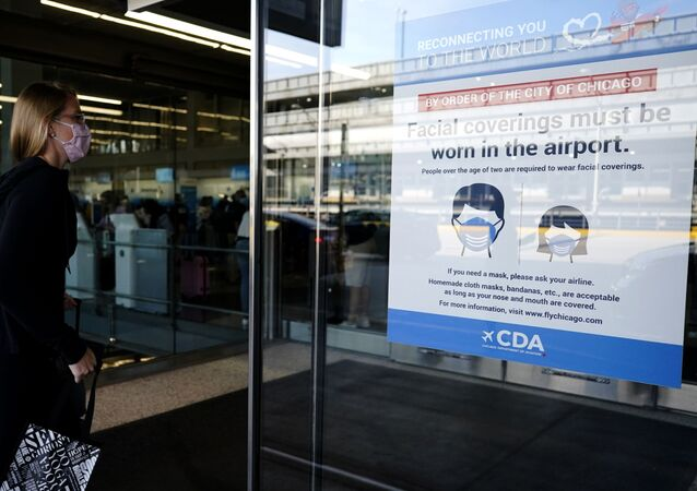 A traveler walks in Terminal 3 as a sign stating face coverings are required is displayed at O'Hare International Airport in Chicago, Friday, July 2, 2021. The World Health Organization is encouraging even the vaccinated to keep masks on, particularly indoors, as the delta variant of COVID-19 ricochets around the world.