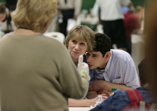 In this August 13, 2014 photograph, Andrew Goldberg rests his head on the shoulder of his mother Louisa as they listen to a therapist in the school cafeteria at the Judge Rotenberg Educational Center in Canton, Massachusetts.  Andrew, who was born with a developmental disorder, wears a electrical shocking device to control violent episodes.
