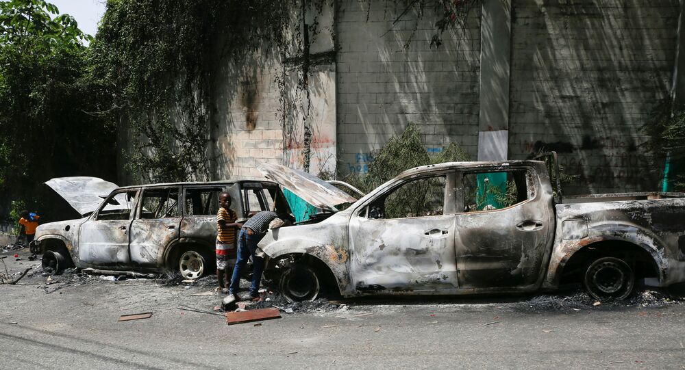 Children look for metal pieces in cars burnt by locals after a firefight between police and the suspected assassins of President Jovenel Moise who was shot dead early Wednesday at his home, in Port-au-Prince, Haiti July 8, 2021.