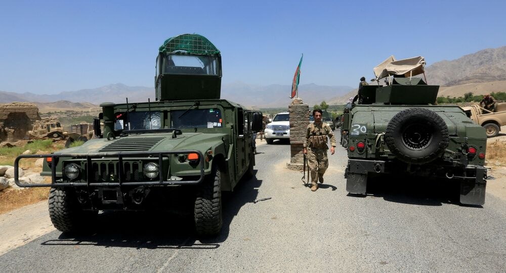 Afghan National Army (ANA) soldiers patrol the area near a checkpoint recaptured from the Taliban, in the Alishing district of Laghman province, Afghanistan, 8 July 2021