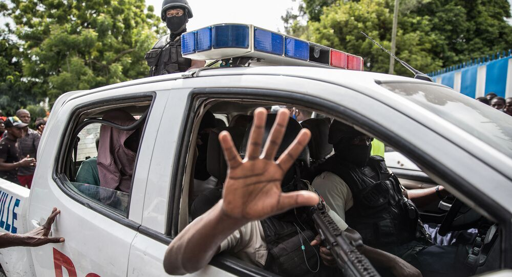 Two men, accused of being involved in the assassination of President Jovenel Moise, are being transported to the Petionville station in a police car in Port au Prince on July 8, 2021