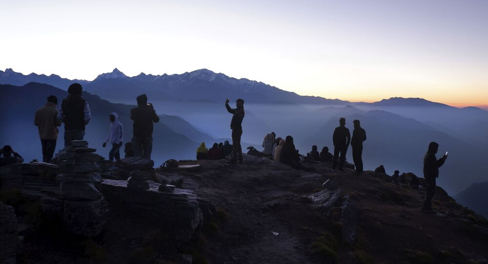 Indian tourists take selfies as other wait to view sun rise at the Chandrashilla Peak in Himalaya at Tungnath in the Indian state of Uttarakhand, Monday, Oct.19, 2020