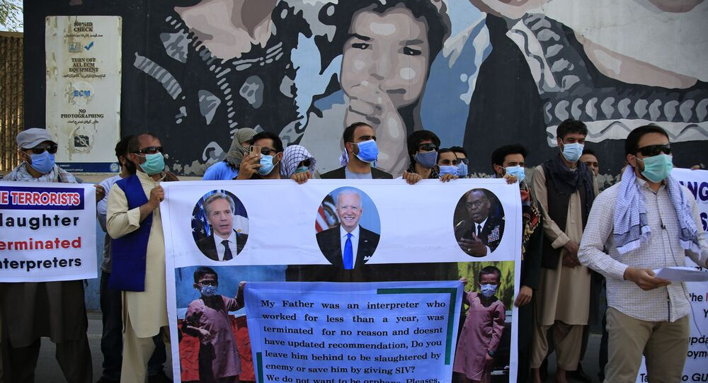 Former Afghan interpreters hold placards during a demonstrations against the US government, in front of the US Embassy in Kabul, Afghanistan, Friday, June 25, 2021.
