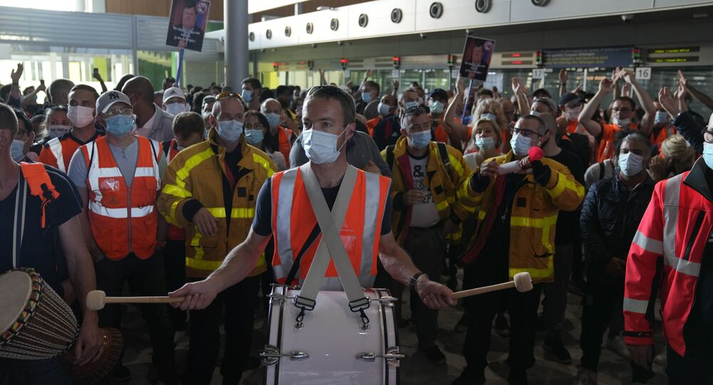 Protesters demonstrate in front of the passport control of Terminal 2E of Charles de Gaulle Airport in Paris, Friday, July 2, 2021. Paris airport workers protesting pay cuts blocked a busy terminal at a Charles de Gaulle Airport and skirmished with police