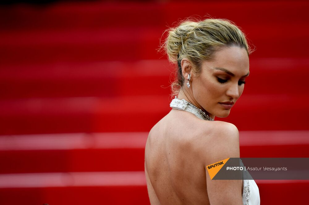 Supermodel Candice Swanepoel wearing a figure-clinching cream number to strut along the red carpet at Cannes Film Festival day two.