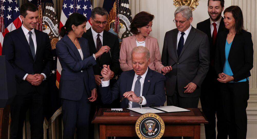 U.S. President Joe Biden hands a pen to Lina Khan, chair of the Federal Trade Commission, while signing an executive order on promoting competition in the American economy, as members of his Cabinet standby in the State Dining Room at the White House in Washington U.S., July 9, 2021.