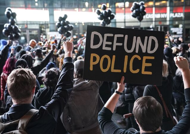 In this 14 October 2020 file photo, a protester holds a sign that reads Defund Police during a rally for the late George Floyd outside Barclays Center in New York
