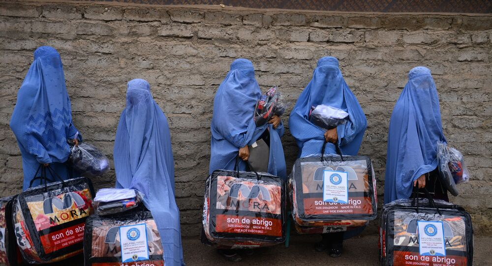 In this photograph taken on December 19, 2019, Afghan burqa-clad women stand with aid items recieved from a charity in Herat.