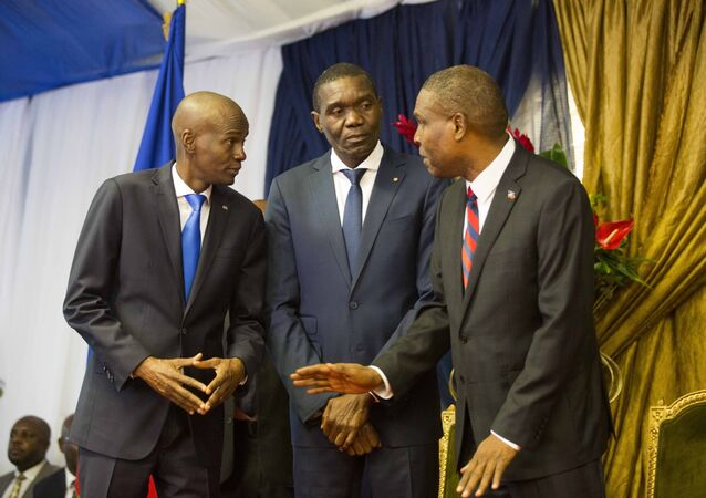 In this Aug. 7, 2018 file photo, Haiti's newly-named Prime Minister Jean-Henry Ceant, right, talks to Haiti's President Jovenel Moise, left, and Senate President Joseph Lambert, during his appointment ceremony at the national Palace in Port-au-Prince, Haiti.