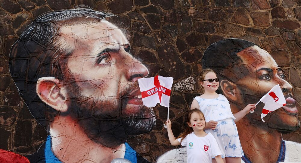 Soccer Football - England fans pose for a photograph in front of a giant mural created by street artist Nathan Parker of Gareth Southgate, Harry Kane and Raheem Sterling ahead of the Euro 2020 final against Italy - Bullring, Nuneaton, Britain - July 10, 2021
