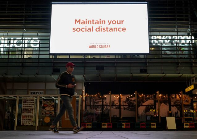 A man walks under a public health message about social distancing displayed at a shopping plaza in the city centre during a lockdown to curb the spread of a coronavirus disease (COVID-19) outbreak in Sydney, Australia