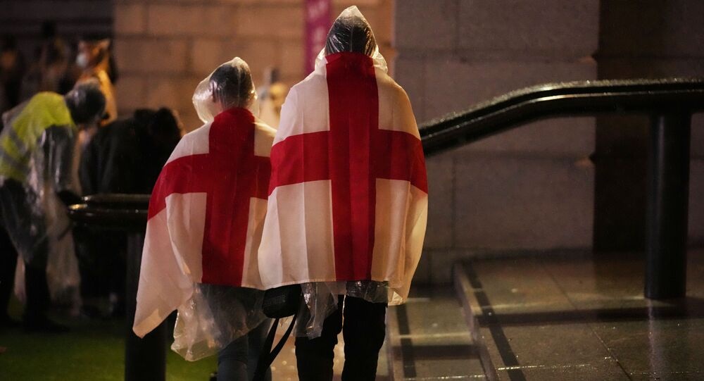 England supporters wear flags as they leave the designated fan zone at Trafalgar Square in London, Sunday, July 11, 2021, after Italy won the Euro 2020 soccer championship final match between England and Italy played at Wembley Stadium.