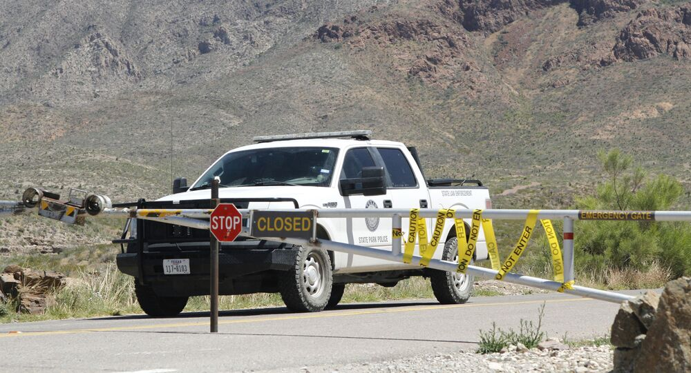 A Texas State Park police officer sits in a patrol truck guarding an entrance to the Franklin Mountains Sunday, April 19, 2020, in El Paso, Texas.