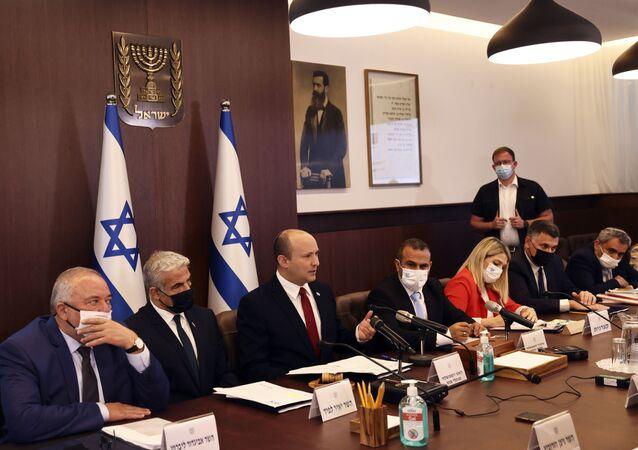 Israeli Prime Minister Naftali Bennett, center, convenes the weekly cabinet meeting, in Jerusalem, Sunday, July 11, 2021.