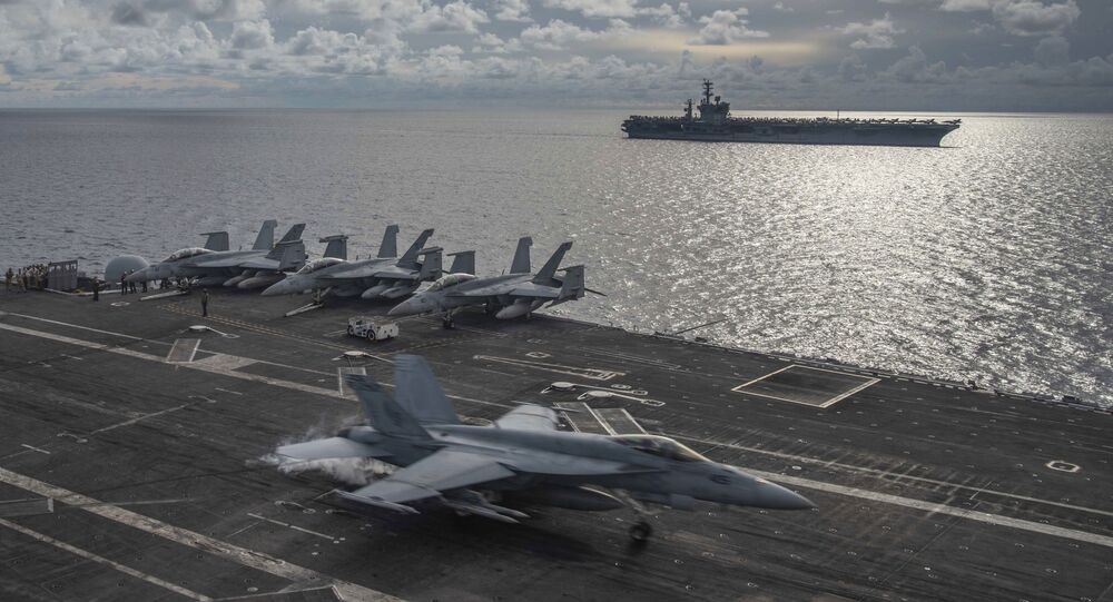 In this photo provided by U.S. Navy, an F/A-18E Super Hornet lands on the flight deck of the USS Ronald Reagan (CVN 76), as USS Nimitz (CVN 68) steams alongside in the South China Sea, Monday, July 6, 2020.