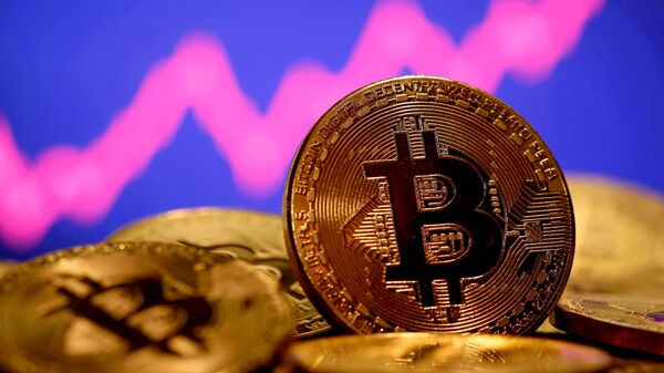 A representation of virtual currency Bitcoin is seen in front of a stock graph in this illustration taken January 8, 2021 - Sputnik International