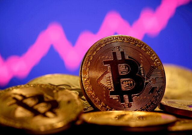 A representation of virtual currency Bitcoin is seen in front of a stock graph in this illustration taken January 8, 2021