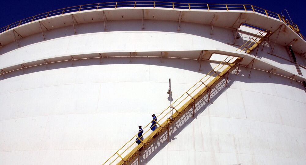 Oil technicians climb down a giant tank at a refinery in Jebel Ali about 30 kms south of Dubai in United Arab Emirates in this file photo taken in March 2004