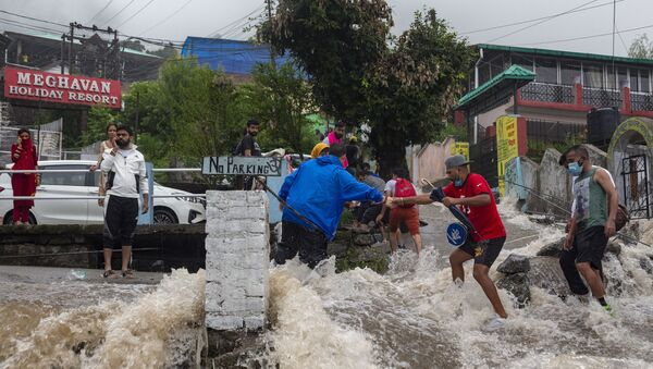 People help each other cross a street amid sudden gush of water during flash floods after heavy monsoon rains in Bhagsunag, a popular tourist town in Himachal Pradesh, India, Monday, July 12, 2021 - Sputnik International