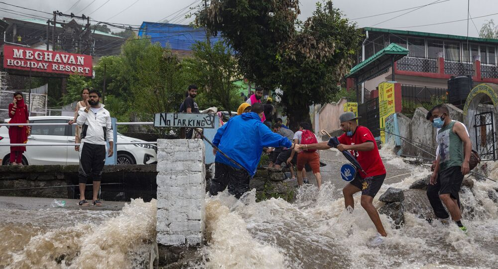 People help each other cross a street amid sudden gush of water during flash floods after heavy monsoon rains in Bhagsunag, a popular tourist town in Himachal Pradesh, India, Monday, July 12, 2021