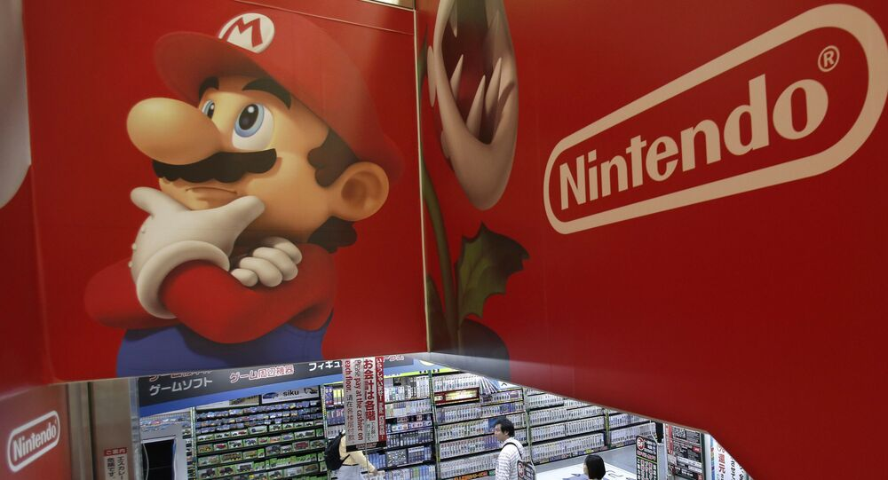 FILE - In this May 7, 2014, file photo, shoppers walk under the logo of Nintendo and Super Mario character, left, at an electronics store in Tokyo. Japanese Prime Minister Shinzo Abe's appearance as Super Mario in the Rio Olympics closing ceremonies on Sunday, Aug. 21, 2016, was a crowd-pleasing reminder of how much the game helped spur on the videogame revolution in the U.S. and globally.