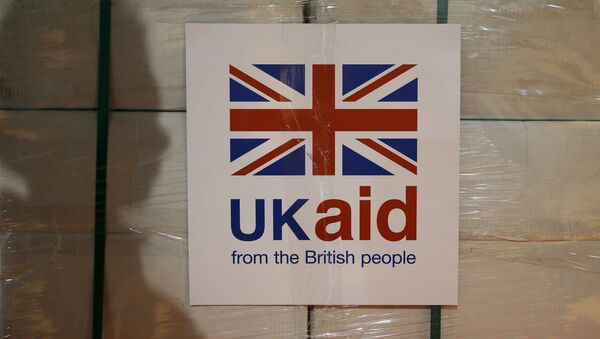 A UK aid label is attatched to a box containing kitchen sets, stored at a UK Aid Disaster Response Centre where humanitarian supplies are being collected to be airlifted to Iraq at Cotswold Airport near the village of Kemble, Gloucestershire, southern England on August 14, 2014 - Sputnik International