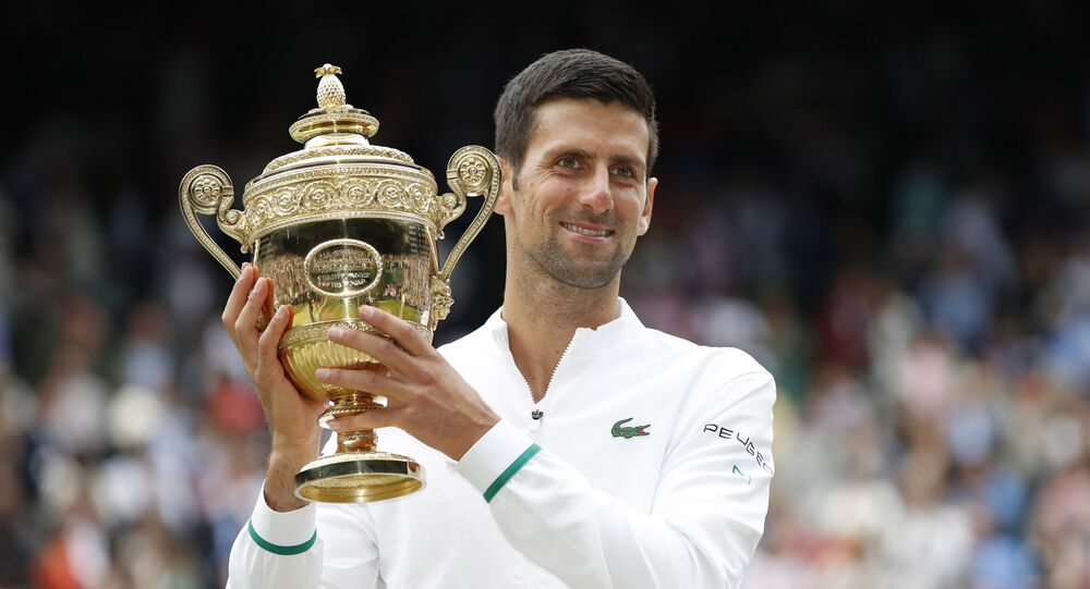 Tennis - Wimbledon - All England Lawn Tennis and Croquet Club, London, Britain - July 11, 2021 Serbia's Novak Djokovic celebrates with the trophy after winning his final match against Italy's Matteo Berrettini