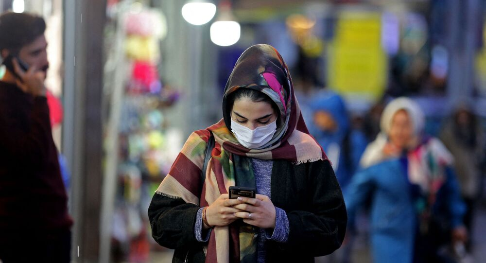 An Iranian woman wearing a protective mask checks her mobile telephone as she walks in a street in the capital Tehran on February 20,2020 (Photo by ATTA KENARE / AFP)