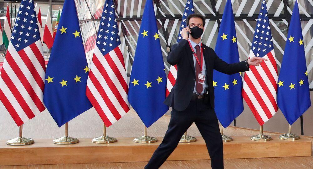 A security guard walks near EU and U.S. flags, before the EU-US summit, in Brussels, Belgium June 15, 2021