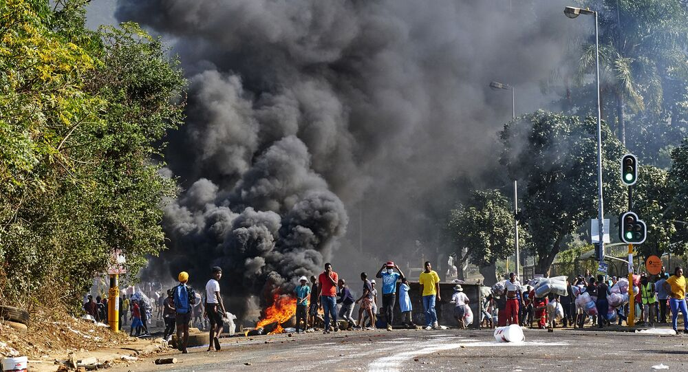 Looters outside a shopping centre alongside a burning barricade in Durban, South Africa, Monday July 12, 2021
