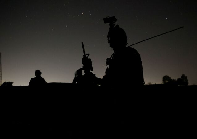 Members of the Afghan Special Forces keep a watch as others search houses in a village during a combat mission against Taliban, in Kandahar province, Afghanistan, July 12, 2021