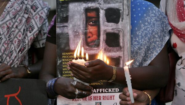 Women hold candles during a protest organized by a non government organization against alleged human trafficking and urged people to be vigilant, in Bangalore, India, Tuesday, March 18, 2008 - Sputnik International