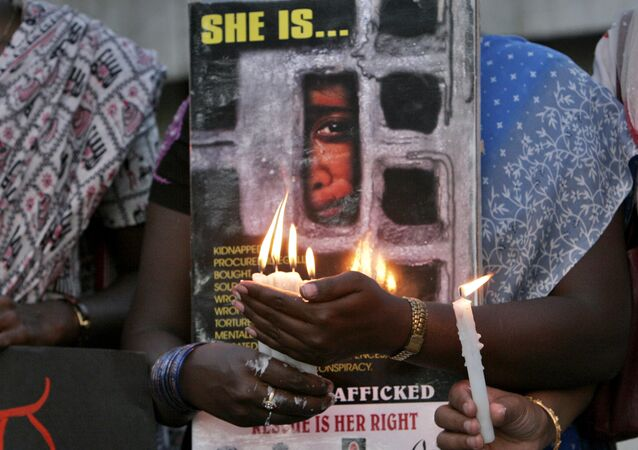 Women hold candles during a protest organized by a non government organization against alleged human trafficking and urged people to be vigilant, in Bangalore, India, Tuesday, March 18, 2008