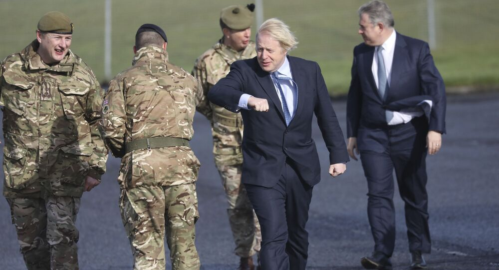 Brandon Lewis accompanies Boris Johnson on a visit to a British armed forces base in Northern Ireland.