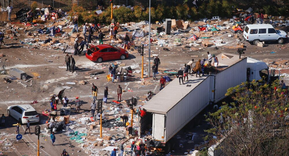 People loot an area near a burning warehouse after violence erupted following the jailing of former South African President Jacob Zuma, in Durban, South Africa, July 14, 2021.