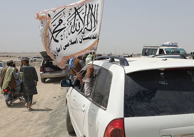 People wave a Taliban flag as they drive through the Pakistani border town of Chaman on July 14, 2021, after the Taliban claimed they had captured the Afghan side of the border crossing of Spin Boldak along the frontier with Pakistan