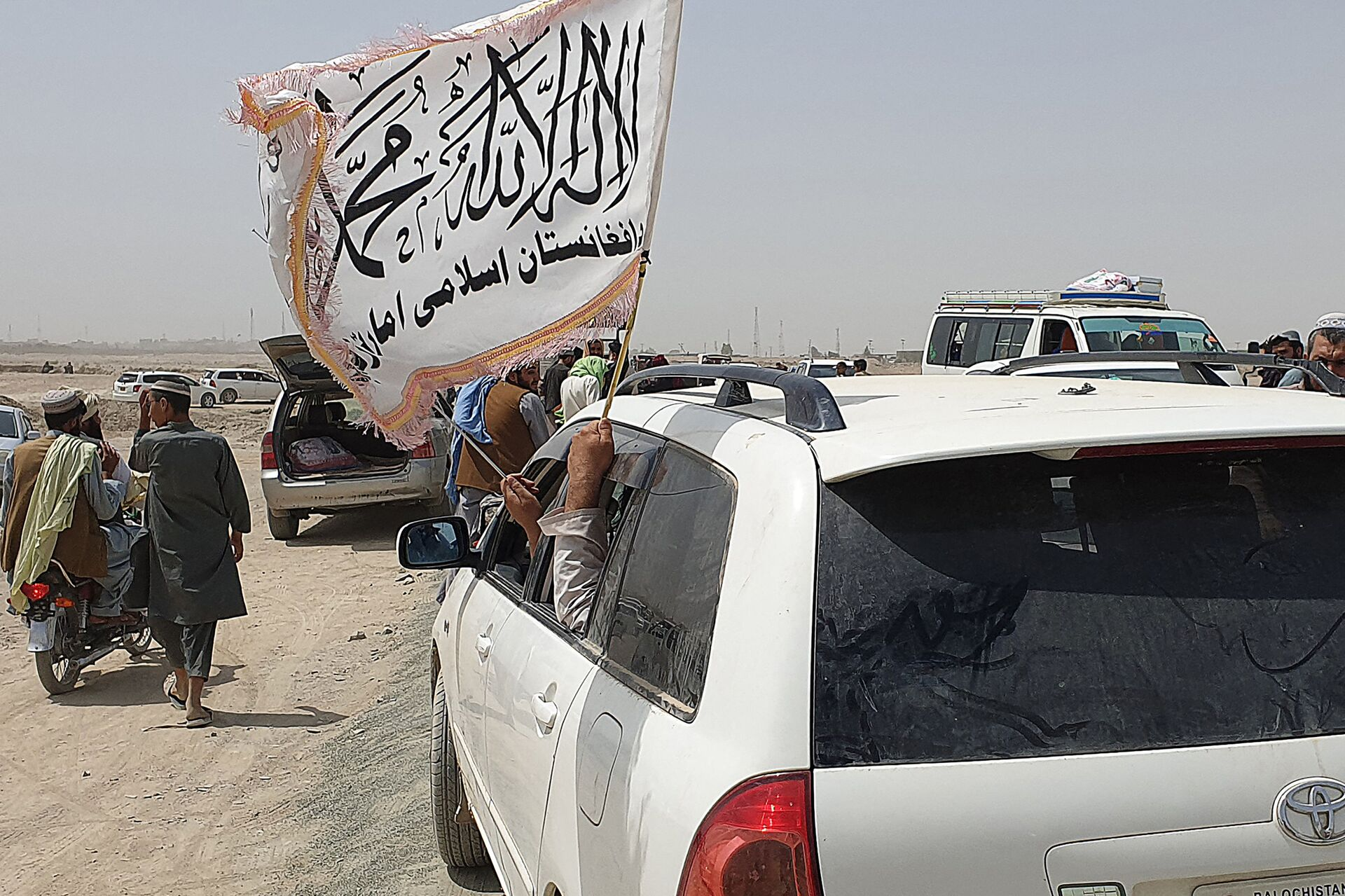 People wave a Taliban flag as they drive through the Pakistani border town of Chaman on July 14, 2021, after the Taliban claimed they had captured the Afghan side of the border crossing of Spin Boldak along the frontier with Pakistan - Sputnik International, 1920, 07.09.2021