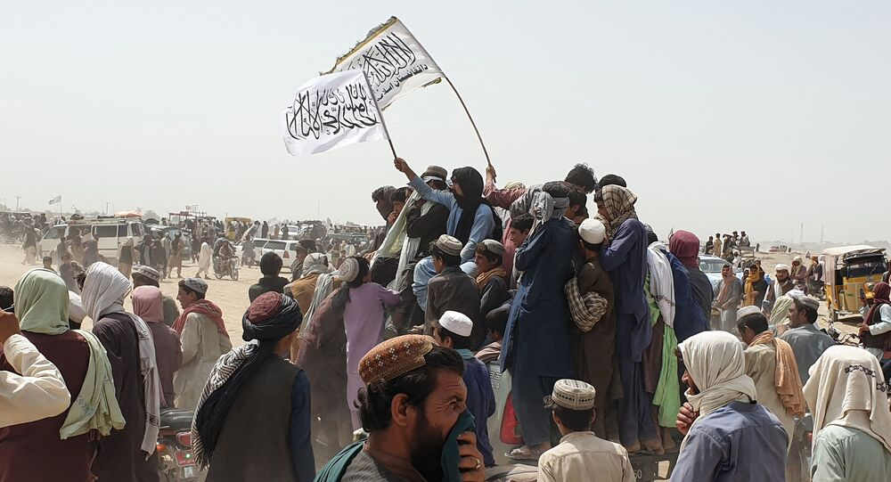 People wave Taliban flags as they drive through the Pakistani border town of Chaman on July 14, 2021, after the Taliban claimed they had captured the Afghan side of the border crossing of Spin Boldak along the frontier with Pakistan