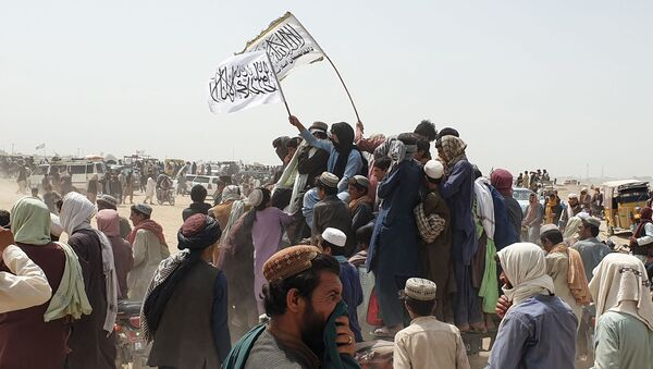 People wave Taliban flags as they drive through the Pakistani border town of Chaman on July 14, 2021, after the Taliban claimed they had captured the Afghan side of the border crossing of Spin Boldak along the frontier with Pakistan - Sputnik International