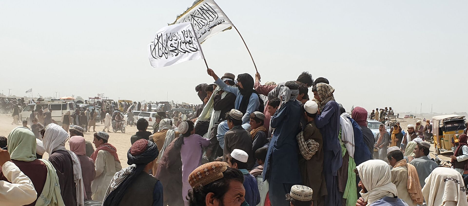 People wave Taliban flags as they drive through the Pakistani border town of Chaman on July 14, 2021, after the Taliban claimed they had captured the Afghan side of the border crossing of Spin Boldak along the frontier with Pakistan - Sputnik International, 1920, 23.07.2021