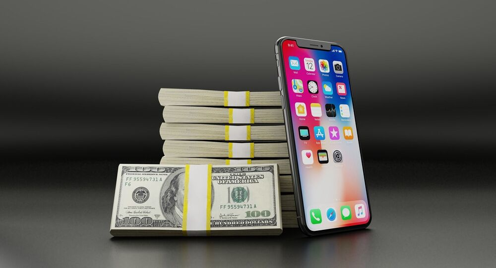 An iPhone placed next to packs of US dollar banknotes.