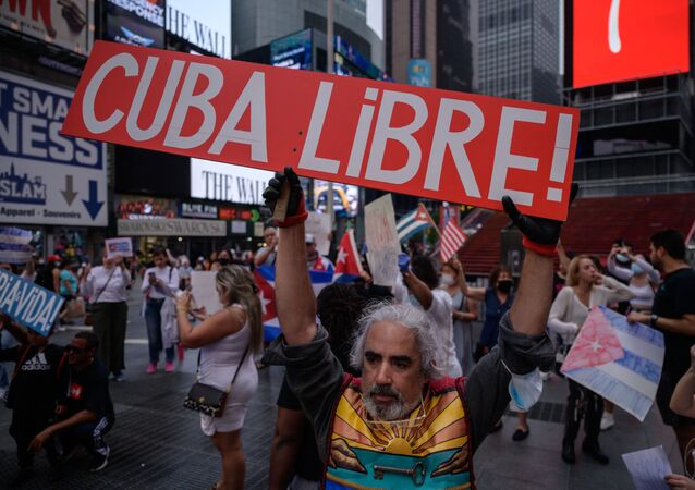 Demonstrators hold placards during a rally held in solidarity with anti-government protests in Cuba, in Times Square, New York on July 13, 2021. - One person died and more than 100 others, including independent journalists and dissidents, have been arrested after unprecedented anti-government protests in Cuba, with some remaining in custody on Tuesday, observers and activists said.