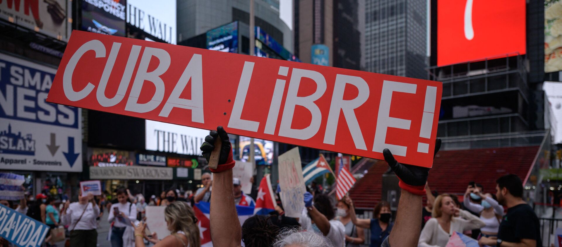 Demonstrators hold placards during a rally held in solidarity with anti-government protests in Cuba, in Times Square, New York on July 13, 2021. - One person died and more than 100 others, including independent journalists and dissidents, have been arrested after unprecedented anti-government protests in Cuba, with some remaining in custody on Tuesday, observers and activists said. - Sputnik International, 1920, 17.07.2021