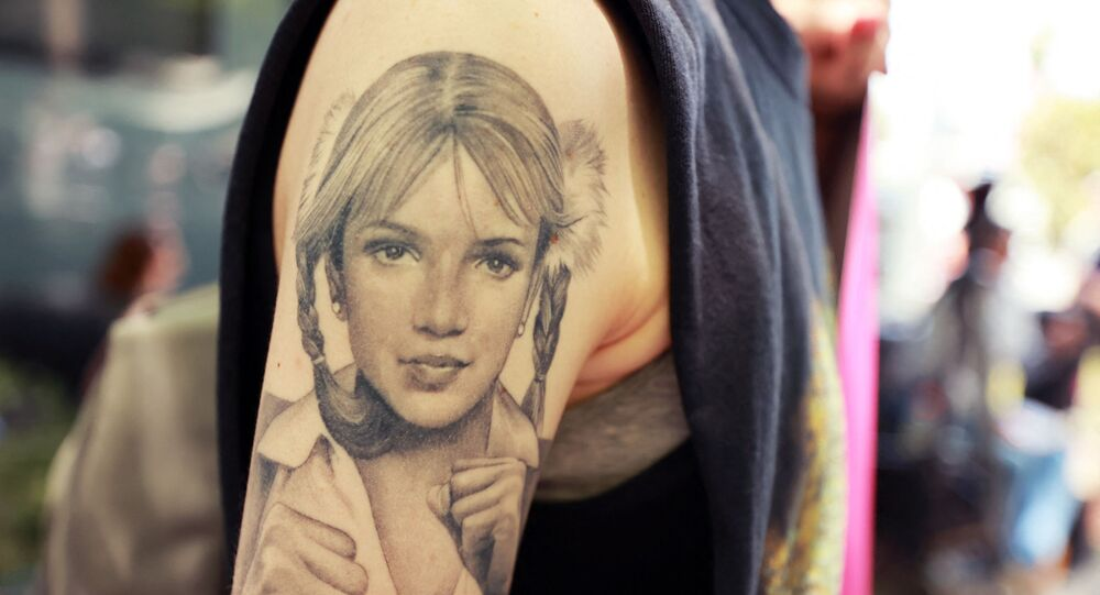 A protester with a Britney Spears tattoo attends a #FreeBritney Rally at Stanley Mosk Courthouse on July 14, 2021 in Los Angeles, California. The group is calling for an end to the 13-year conservatorship lead by the pop star's father, Jamie Spears and Jodi Montgomery, who have control over her finances and business dealings. Planned co-conservator Bessemer Trust is petitioning the court to resign from its position after Britney Spears spoke out in court about the conservatorship.