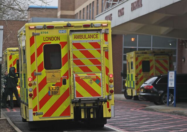 Ambulances are parked at the emergency arrival at Charing Cross hospital in London, Friday, Jan. 8, 2021