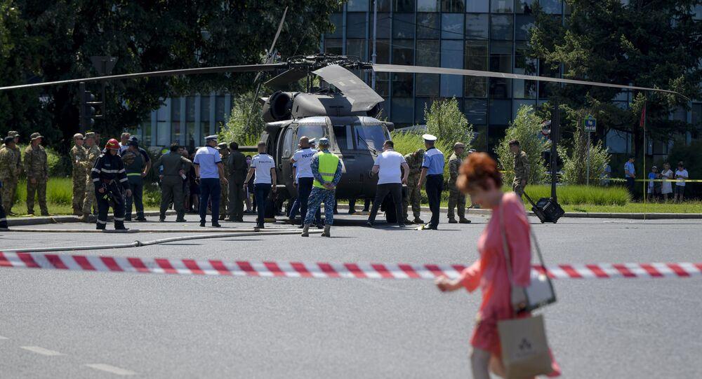 Servicemen walk by a U.S military Black Hawk helicopter following an emergency landing on a busy boulevard, in Bucharest, Romania, Thursday, July 15, 2021