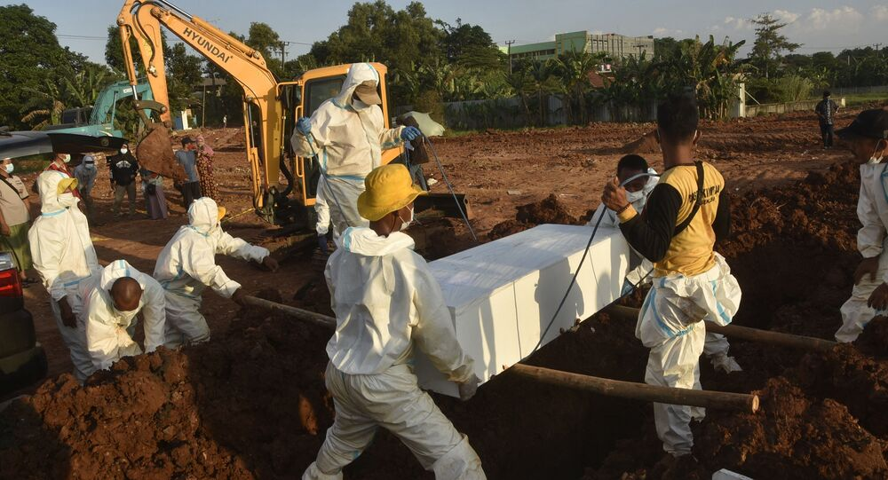 Gravediggers wearing personal protective equipment carry a coffin for burial at a cemetery in Bekasi on July 12, 2021, as Indonesia faces its most serious outbreak driven by the highly infectious Delta variant of Covid-19
