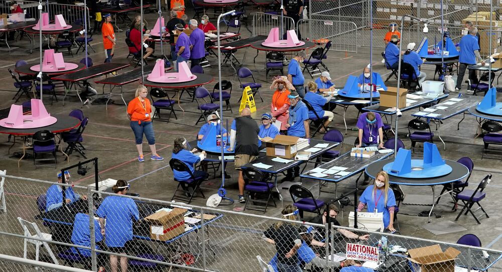 In this May 6, 2021, file photo, Maricopa County ballots cast in the 2020 general election are examined and recounted by contractors working for Florida-based company, Cyber Ninjas at Veterans Memorial Coliseum in Phoenix. Arizona's largest county has approved nearly $3 million for new vote-counting machines to replace those given to legislative Republicans for a partisan review of the 2020 election. The GOP-controlled Maricopa County Board of Supervisors said Wednesday, July 14, 2021 that the machines were compromised because they were in the control of firms not accredited to handle election equipment. (AP Photo/Matt York, Pool, File)